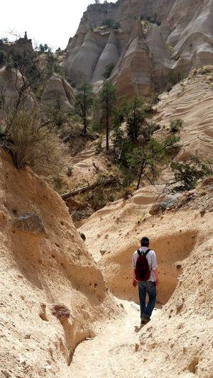Rear View Of Man Walking On Walkway Against Mountain