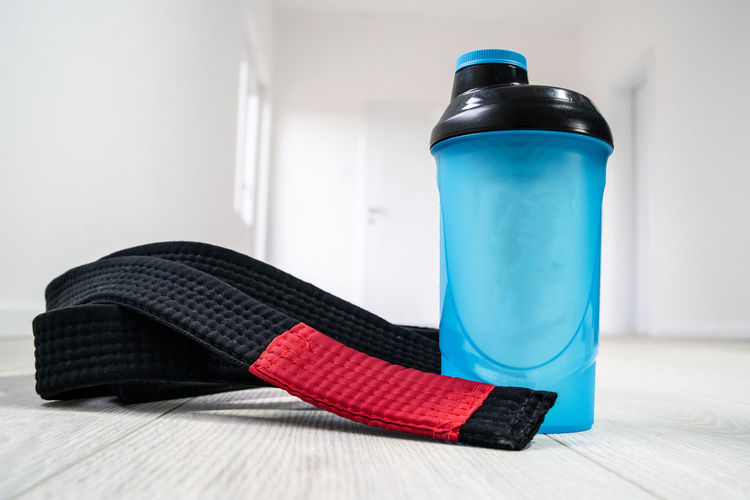 Blue Indoors  Flooring Still Life Shoe Table Red Close-up No People Lifestyles Home Interior Wood Bottle Focus On Foreground Hardwood Floor Day Healthy Lifestyle Exercising Container Single Object Personal Accessory