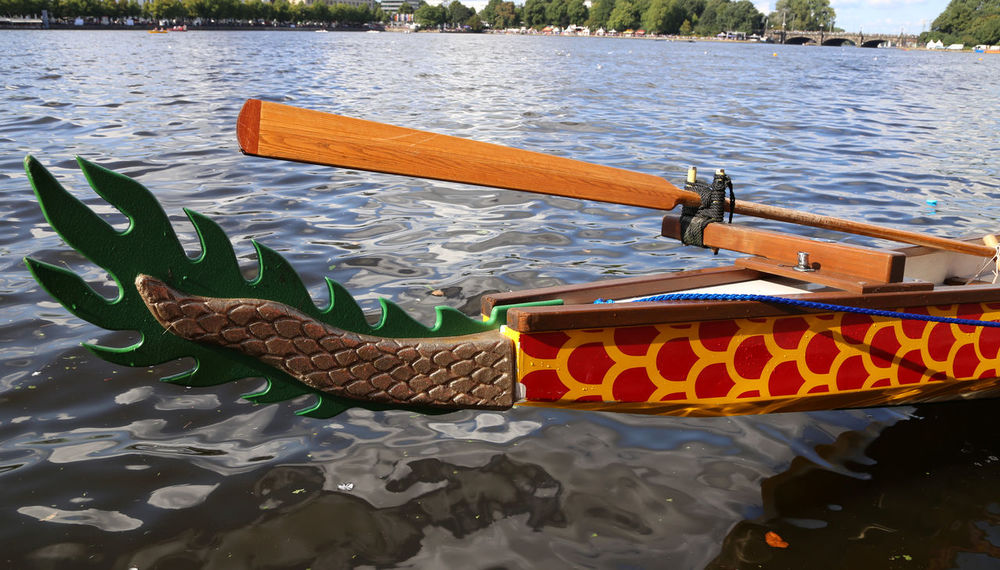 Dragon boat on Hamburg Alster lake (Binnenalster) Dragon Boat Festival Beauty In Nature Boat Day Dragon Boat Floating On Water Gondola - Traditional Boat Lake Mode Of Transport Moored Nature Nautical Vessel No People Oar Outdoors Paper Boat Pedal Boat Raft Rowboat Rowing Sailing Transportation Water Waterfront Wood - Material