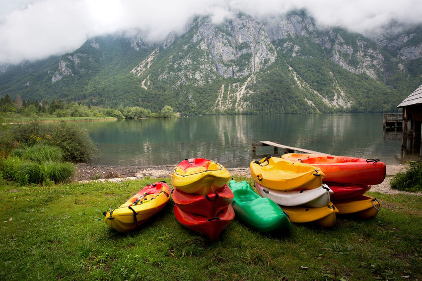 Slovenia Water Lake Mountain Nature Day Scenics - Nature Multi Colored Mountain Range Plant Kayak Beauty In Nature Tranquility No People Cloud - Sky Transportation Tranquil Scene Adventure Grass Outdoors Nature Outdoor Sports Kayaks Many Lakeside Outdoor Activity