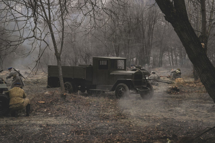 Armed forces by abandoned cars on field in forest