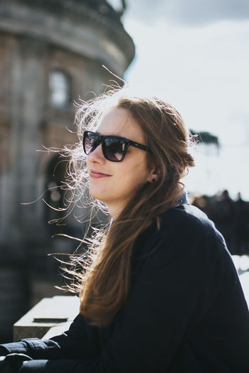 Portrait of young woman in sunglasses against sky