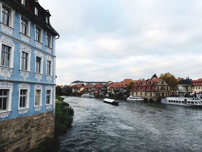 River amidst buildings in city against sky