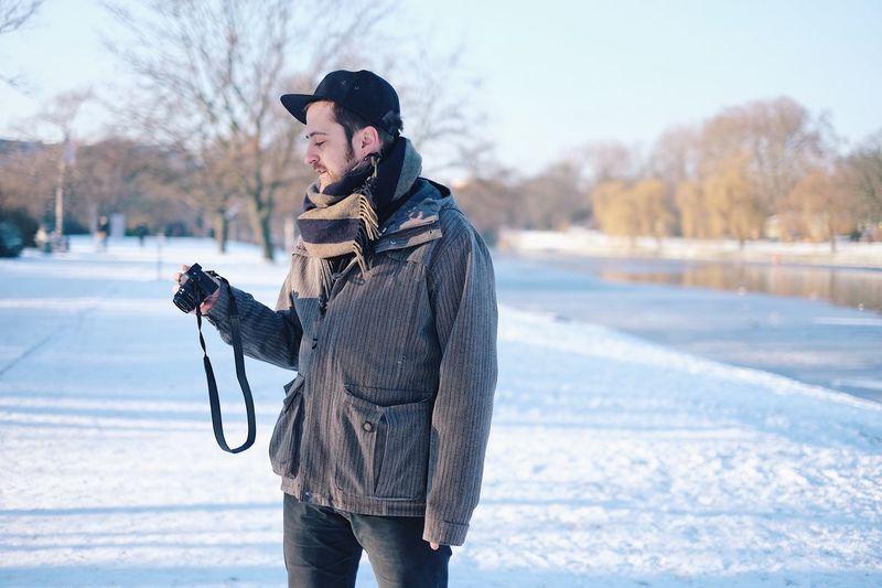 Man holding camera on street in snow