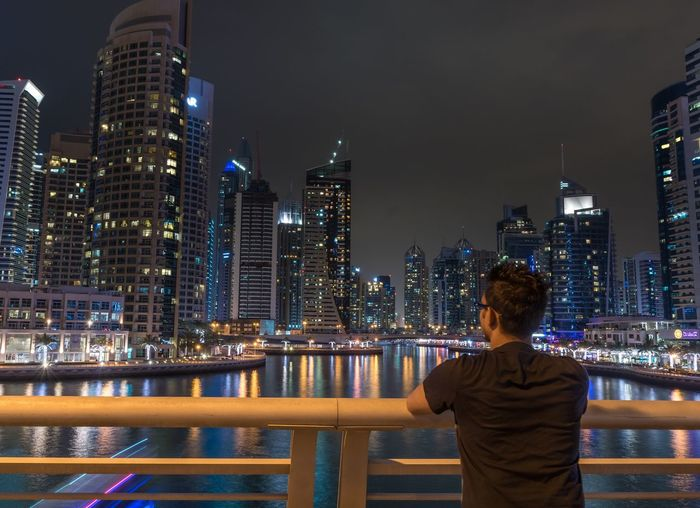 Rear view of man looking at illuminated modern buildings in city at night