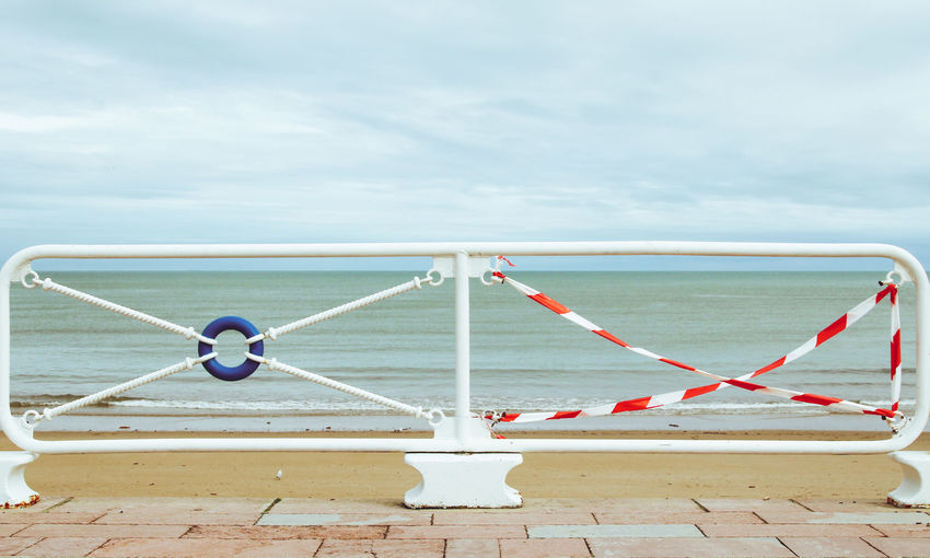 Metallic railing by sea against sky