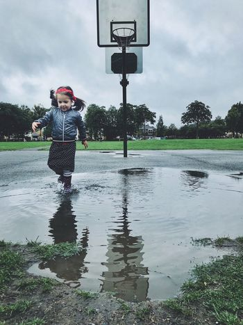 Girl Kid Basketball Puddle Wellies  Water Sky One Person Cloud - Sky Nature Real People Childhood Child Rain Outdoors Rainy Season Reflection Full Length
