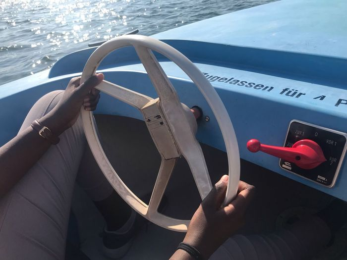 Close-up of man driving boat in sea