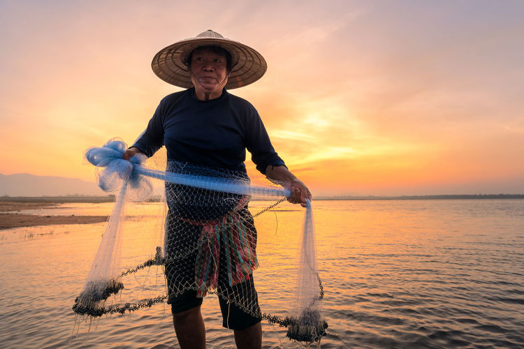 Fisherman holding fishing net while standing in lake against sky