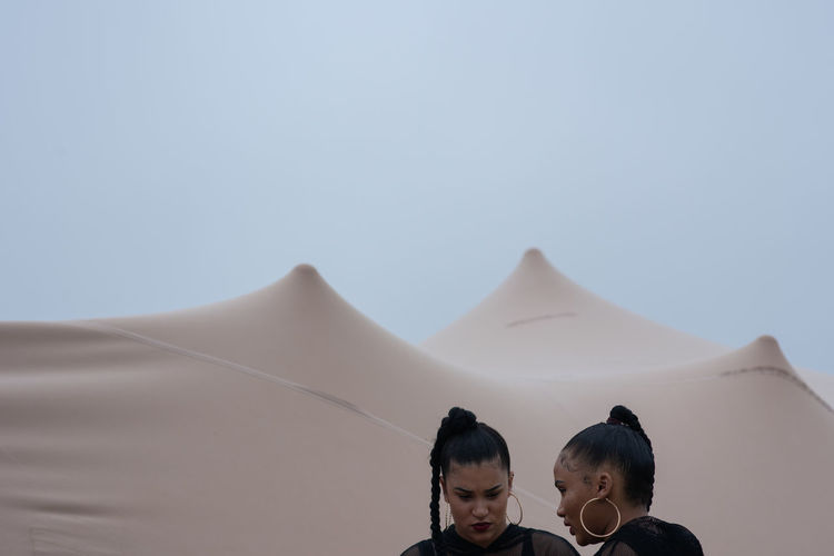 Close-up of two women at desert against clear sky