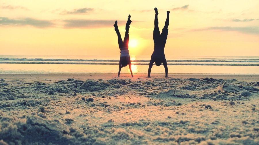 Full length of friends doing handstand at sandy beach against orange sky