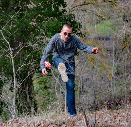 Young man kicking beer can in forest