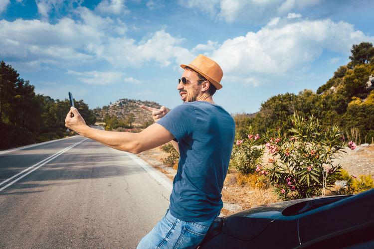 Man standing on road against sky