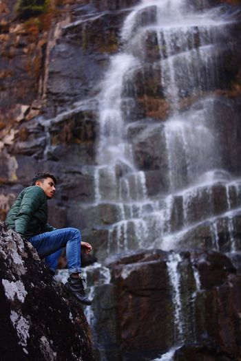 Low angle view of woman sitting on rock against waterfall