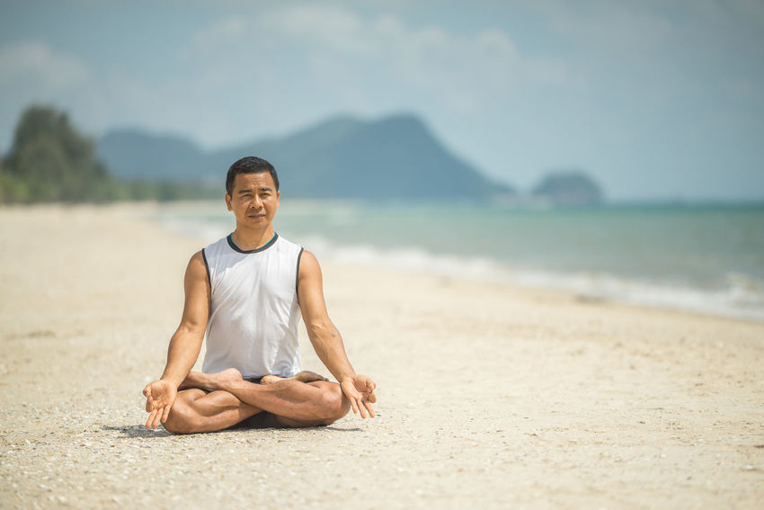 Beach Beauty In Nature Cross-legged Day Focus On Foreground Full Length Happiness Healthy Lifestyle Leisure Activity Lifestyles Looking At Camera Lotus Position Nature One Person Outdoors Real People Relaxation Sand Scenics Sea Sky Smiling Tranquil Scene Wellbeing Yoga