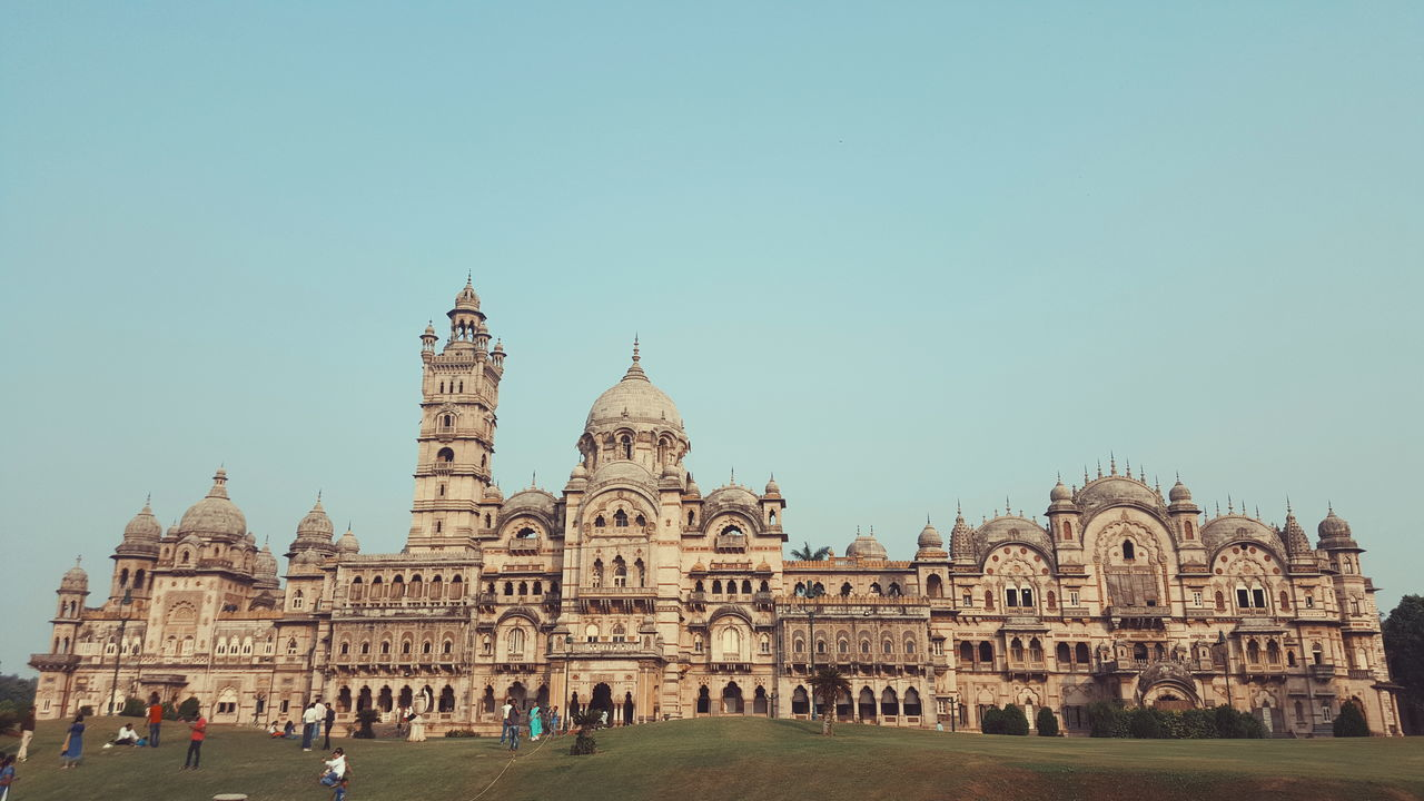 architecture, built structure, tourism, large group of people, building exterior, travel, history, religion, travel destinations, clear sky, real people, spirituality, day, place of worship, leisure activity, outdoors, dome, vacations, men, lifestyles, sky, ancient civilization, nature, people