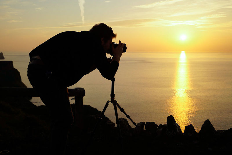 Silhouette man photographing sea against sky during sunset