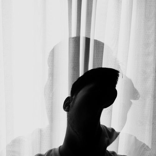Double exposure of man and curtain