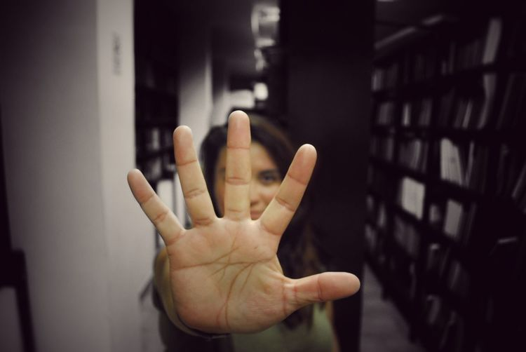 Close-up of woman showing stop gesture in library