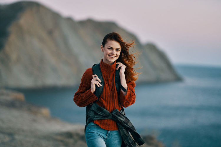 Portrait of smiling young woman standing against sea
