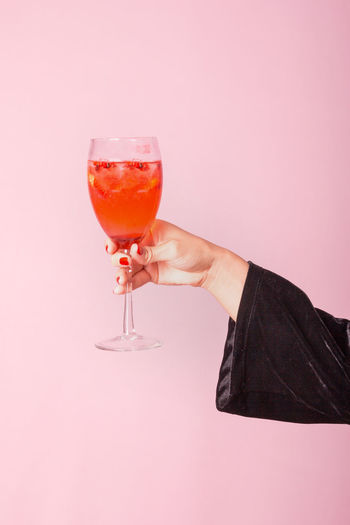 Midsection of man holding drink against white background