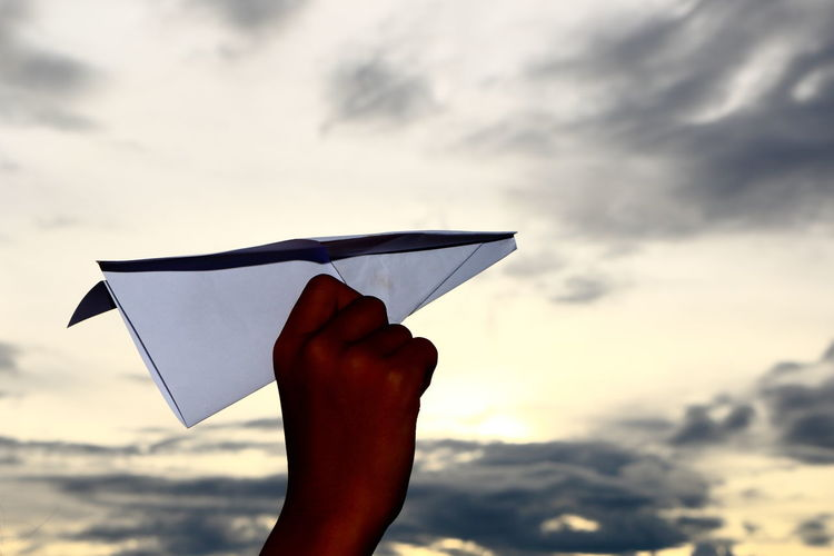 Cropped hand of girl flying paper airplane against sky
