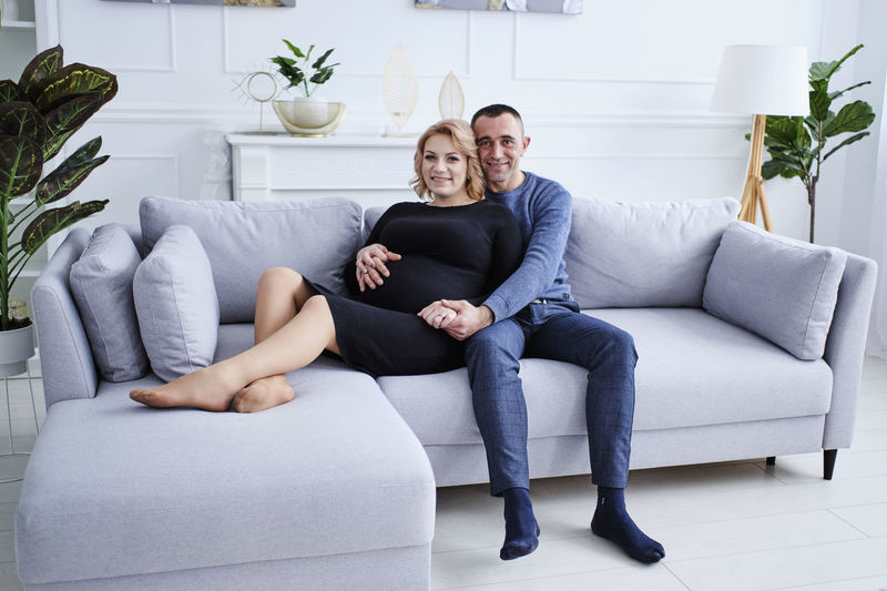 Portrait of a smiling young couple sitting on sofa