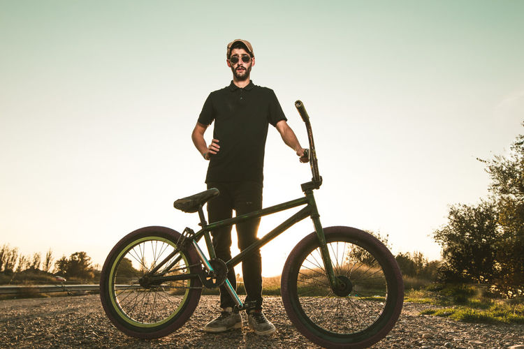Young Man With Bicycle Standing On Field Against Clear Sky During Sunset