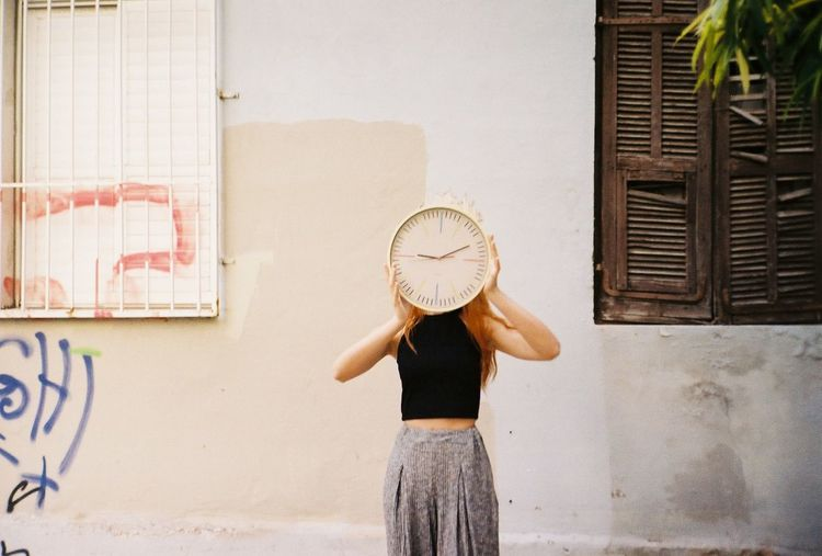 Woman Holding Clock While Standing Against Wall