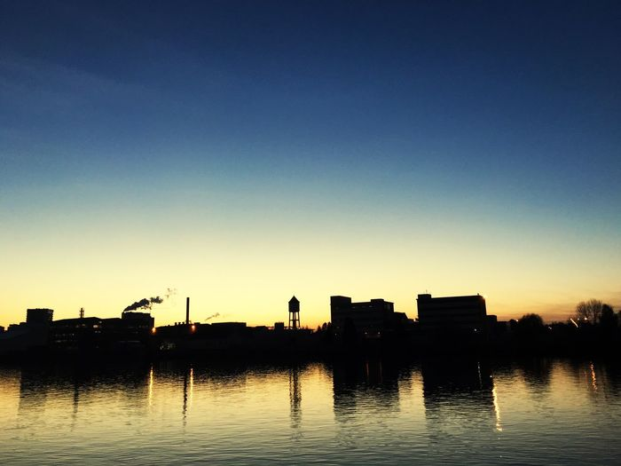 Silhouette built structures with waterfront at sunset
