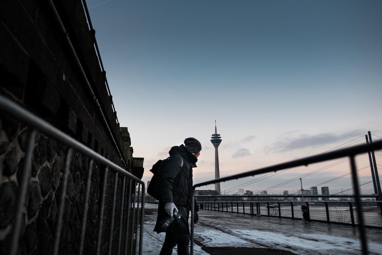 Man holding camera standing on promenade against rheinturm tower during winter