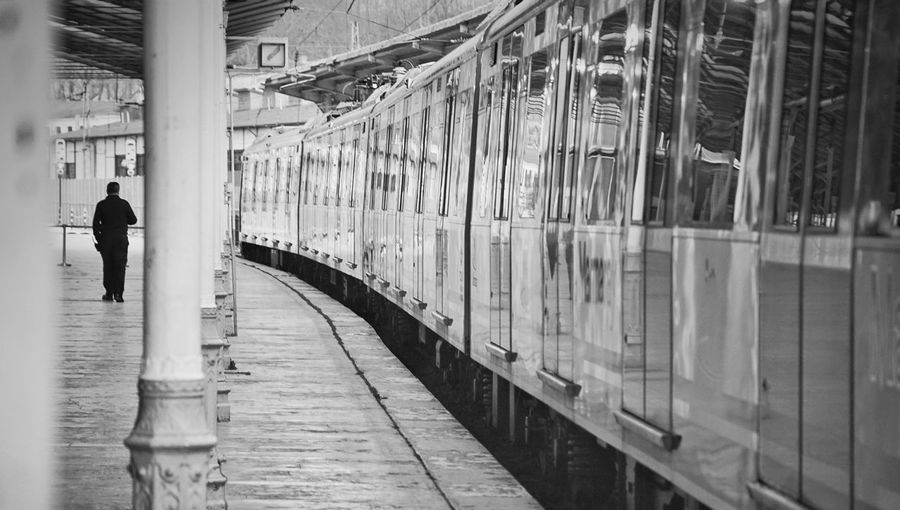 Rear view of woman walking on railway station platform