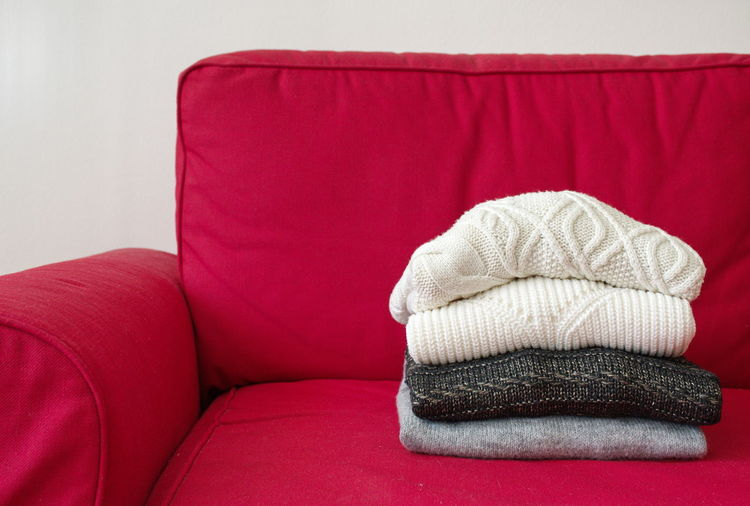 Closeup shot of warm sweaters on red sofa in living room