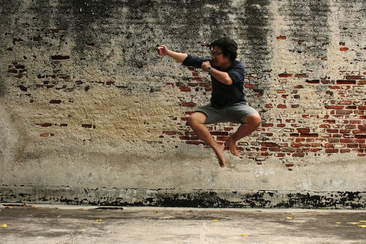 Man gesturing while jumping against old brick wall