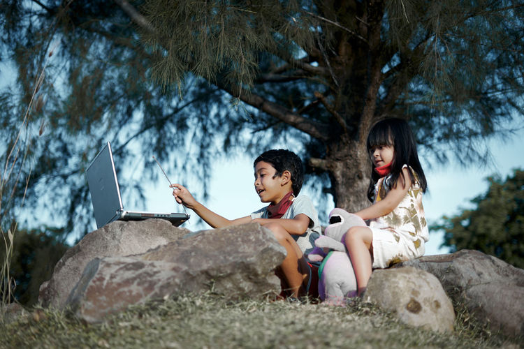 Women sitting on rock against trees