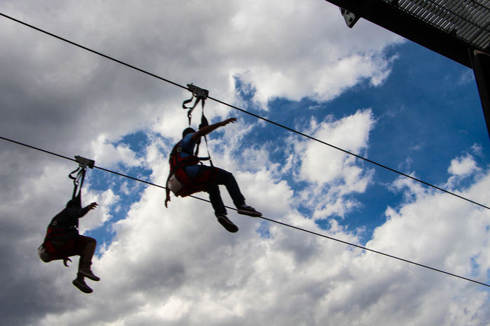 Fun fun fun !!! Adventure Cable Carefree Clothesline Cloud - Sky Cloudy Day Hanging In A Row Laundry Low Angle View Outdoors Power Line  Rope Safety Harness Shoe Sky Two Is Better Than One Zip Line Ziplining The Color Of Sport People And Places Fun