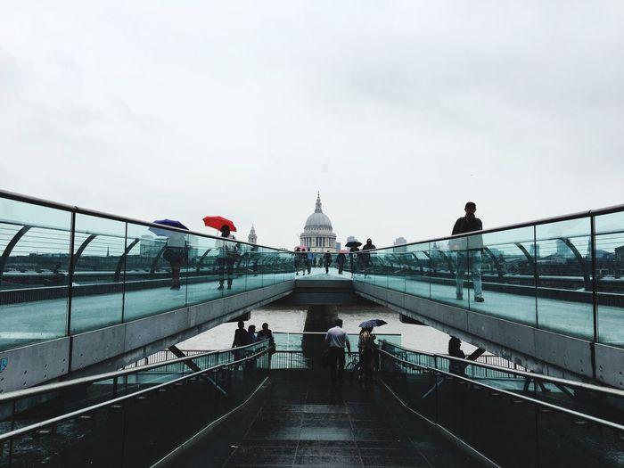 People walking on footbridge against cloudy sky in city