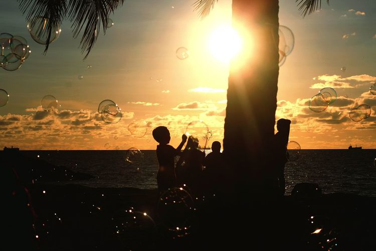 Live For The Story Silhouette Sunset Sea Beach Fun Leisure Activity People Lifestyles Outdoors Vacations Real People Low Angle View Street Photography Eye Of Borneo Shore