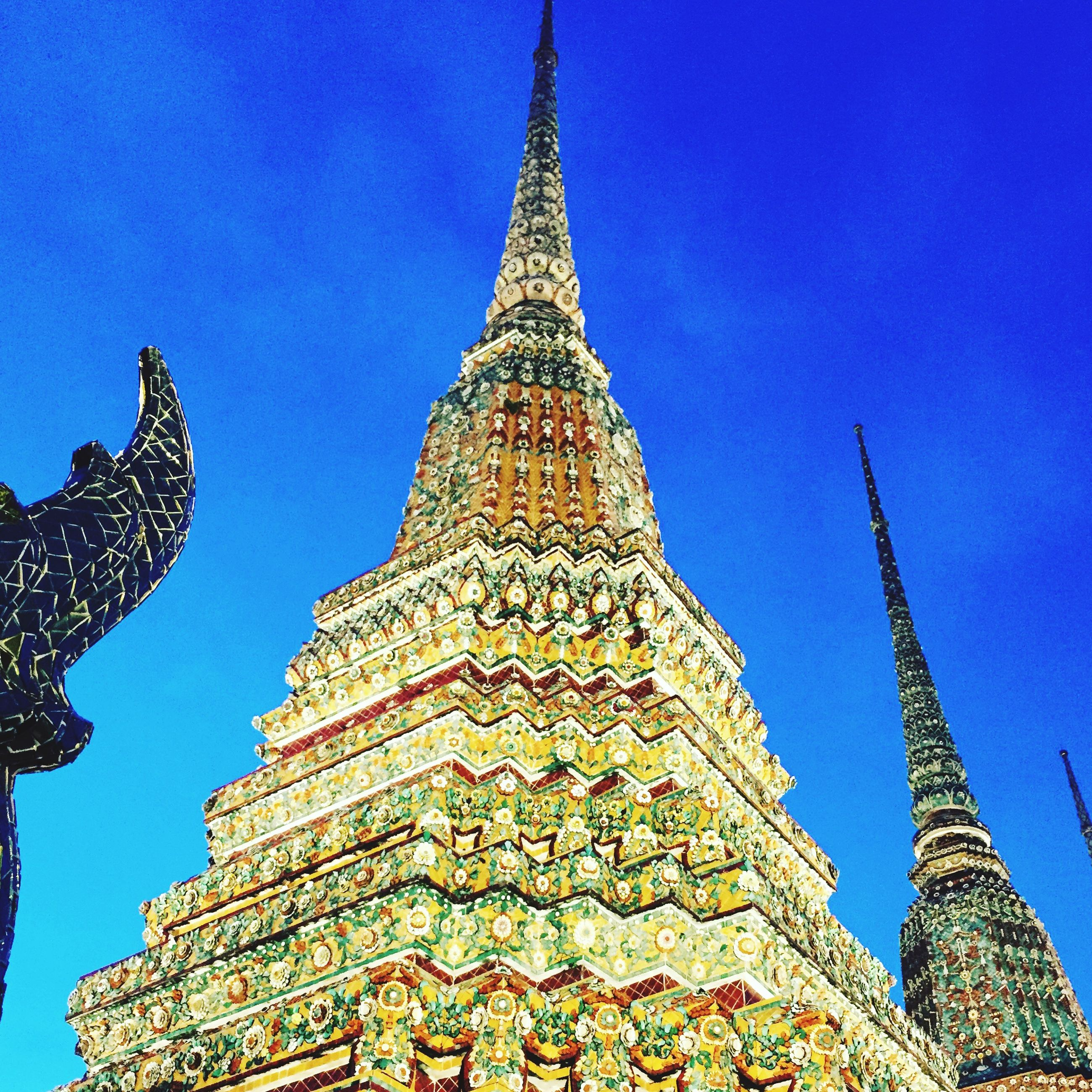 low angle view, blue, clear sky, religion, famous place, gold colored, spirituality, design, place of worship, travel, travel destinations, pattern, cultures, temple - building, tourism, international landmark, art and craft, temple, outdoors