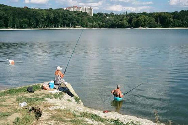 Men fishing in sea against sky