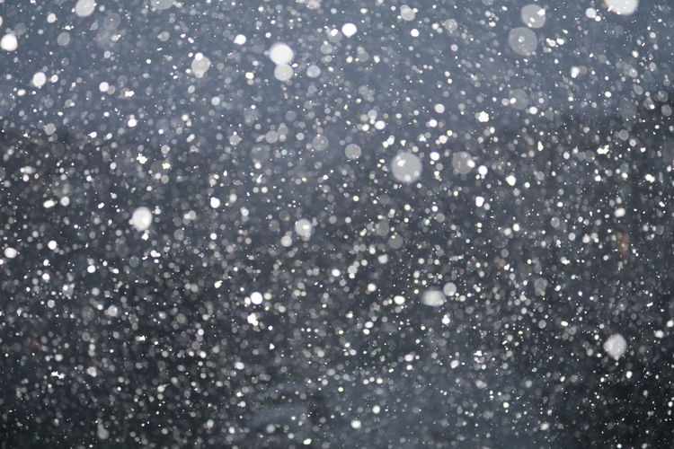 Snowing against sky at night