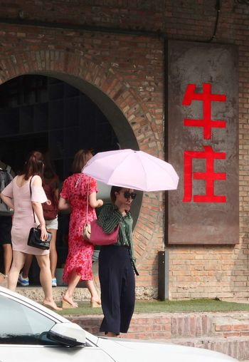 Woman standing with red umbrella