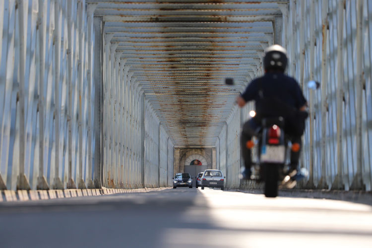 View of sunlit interior of metal bridge with motorcycle in foreground with illusion