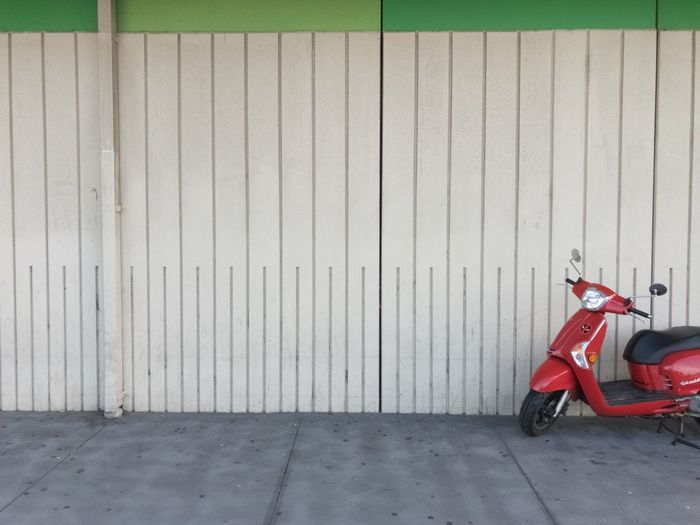 Motor scooter parked by wall
