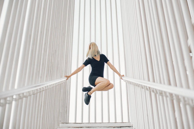 Low Angle View Of Woman Jumping While Holding Railings Against Architectural Column