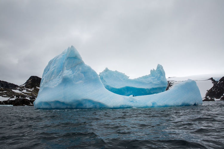 Scenic view of iceberg floating on sea against sky