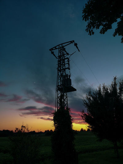 Low angle view of silhouette communications tower against sky during sunset