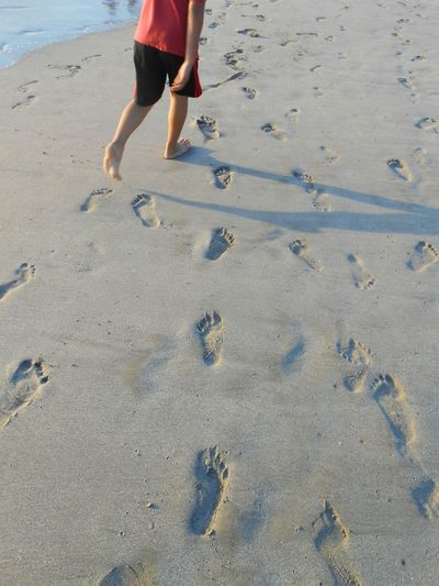 Low section of boy walking on sand at beach