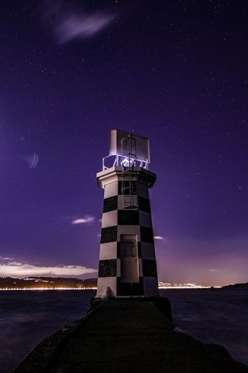 Architecture Astronomy Building Exterior Built Structure Direction Guidance Illuminated Lighthouse Nature Night No People Outdoors Protection Purple Safety Scenics - Nature Sea Security Sky Space Space And Astronomy Star - Space Tower Water