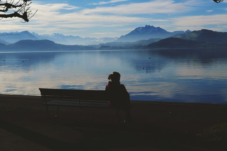 Woman sitting on seat by lake against sky in switzerland